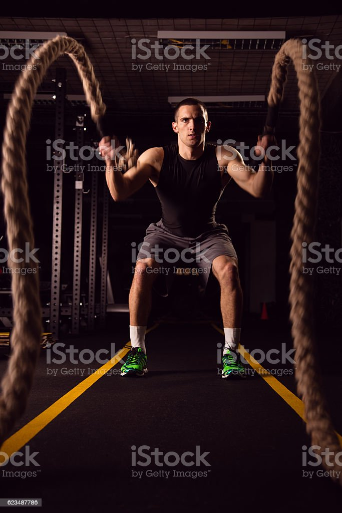 Young man on crossfit training with ropes stock photo