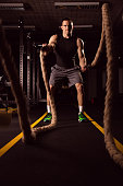 Young man on gym training with ropes