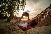 Young man on hammock with digital tablet-Tropical beach