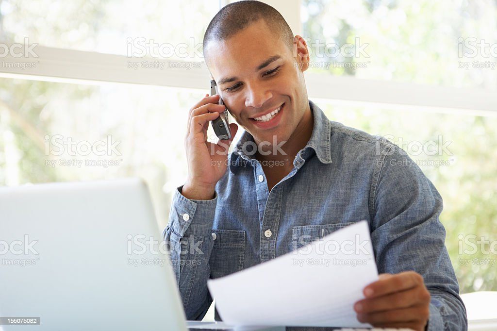 A young man on his phone with a laptop and paperwork stock photo