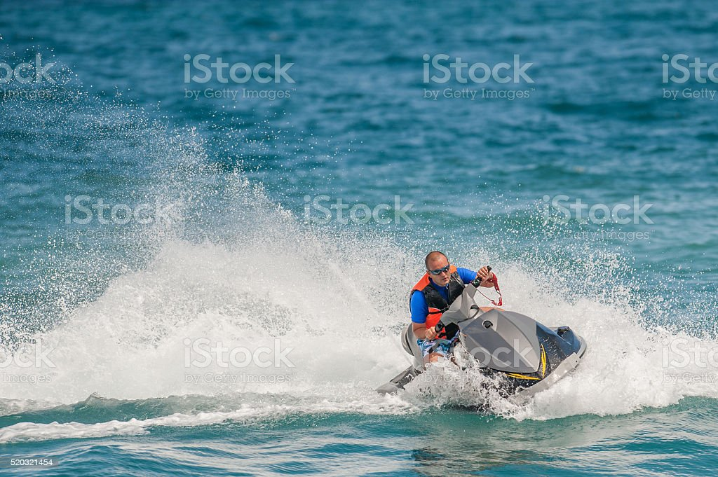 Young Man on Jet Ski, Tropical Ocean, Vacation Concept stock photo