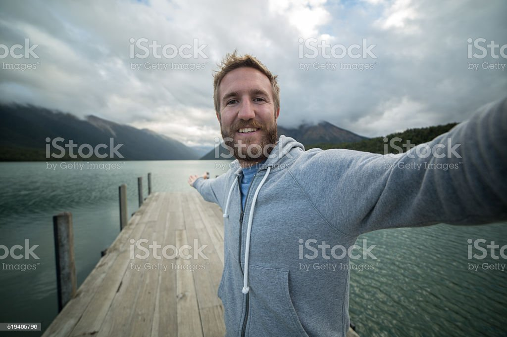 Young man on lake pier, takes selfie using mobile phone stock photo