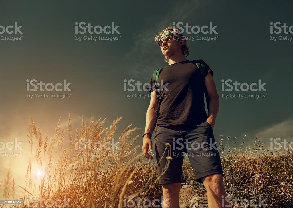 Young man on mountain hill stock photo