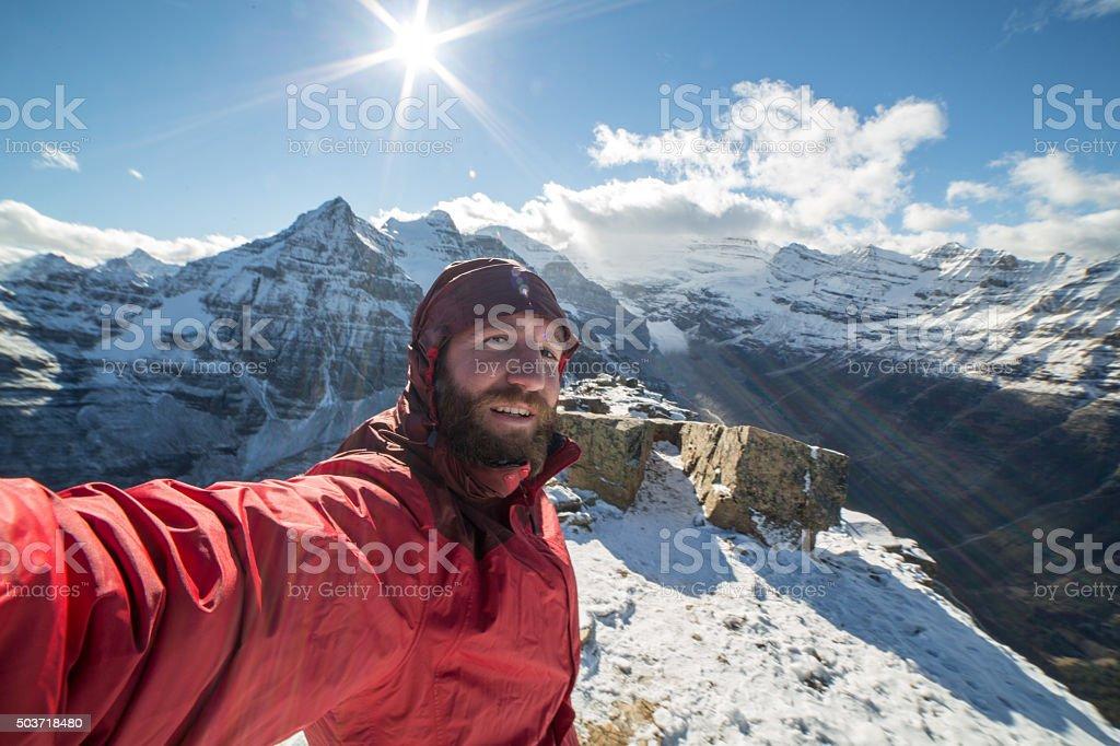 Young man on mountain peak takes a selfie portrait stock photo