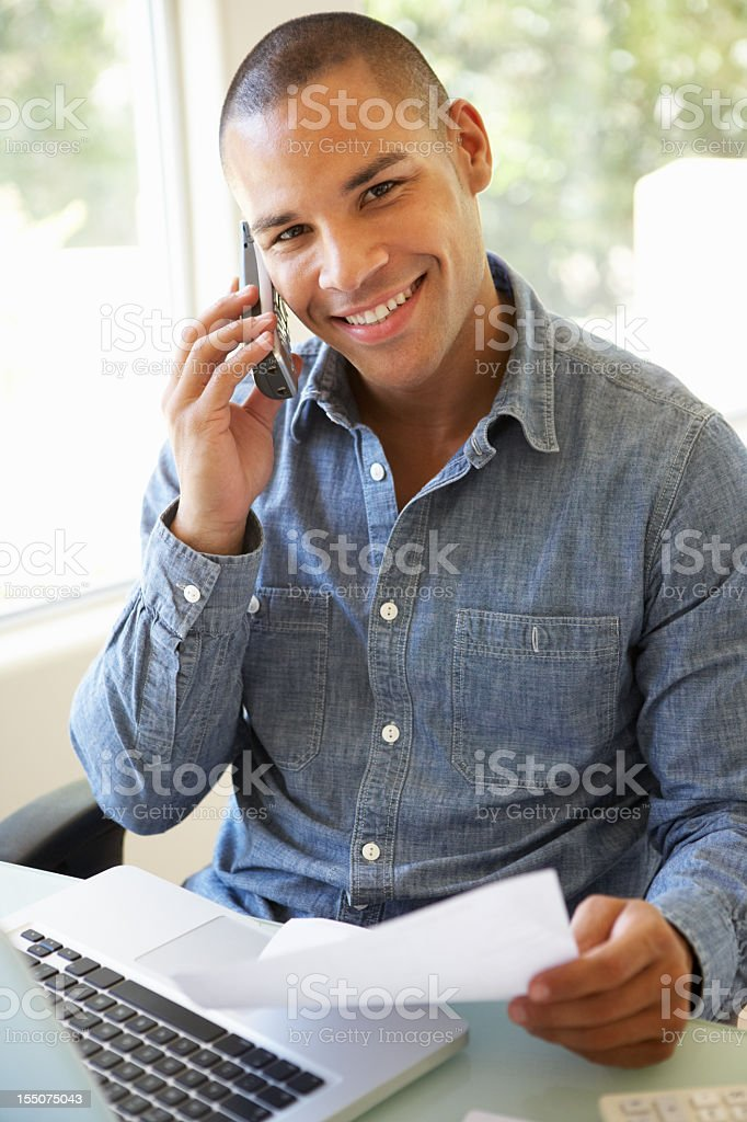 Young Man On Phone Using Laptop At Home royalty-free stock photo