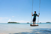 Young man on rope swing above sea beach