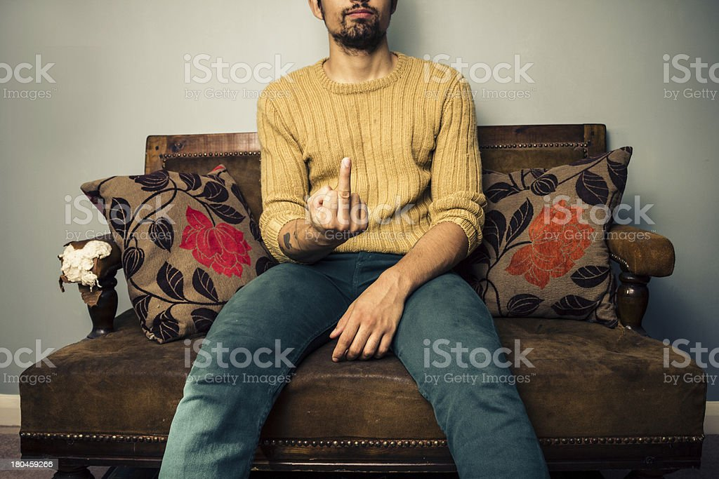 Young man on sofa displaying obscene gesture royalty-free stock photo