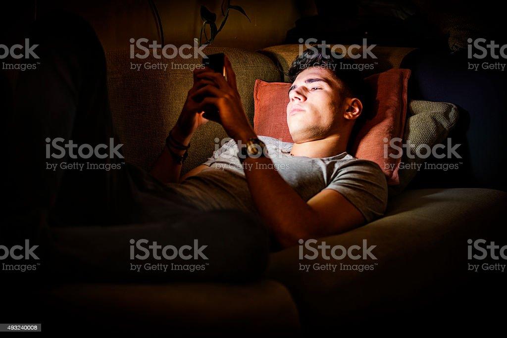 Young Man on Sofa Lit by Light from Cell Phone stock photo