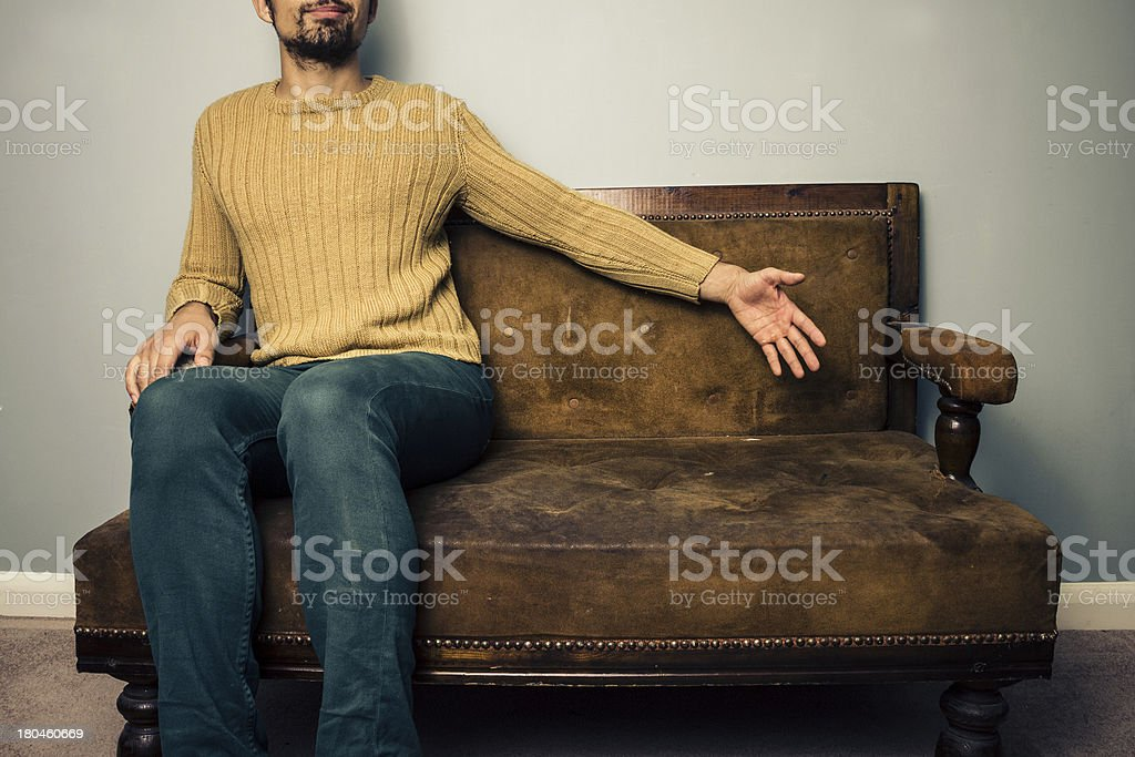 Young man on sofa offering up a seat royalty-free stock photo
