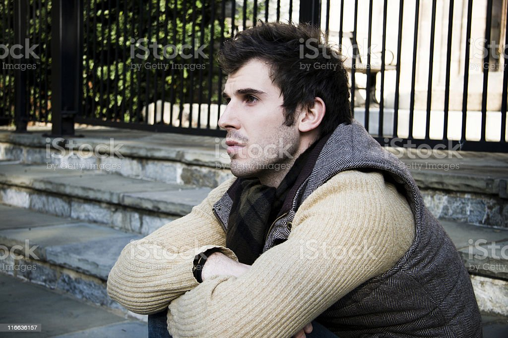 Young man on stairs looking pensive stock photo