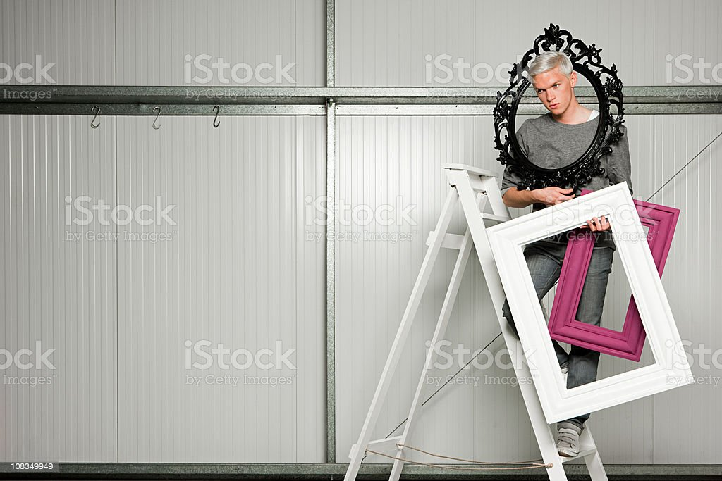 Young man on stepladders carrying picture frames royalty-free stock photo