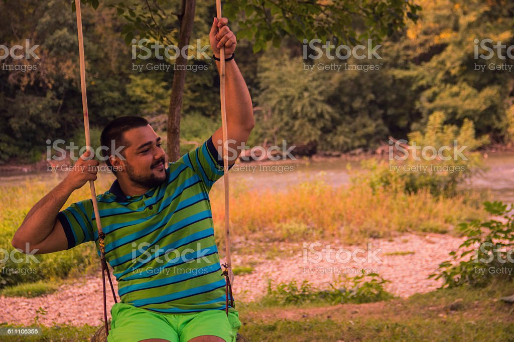 Young man on swing royalty-free stock photo