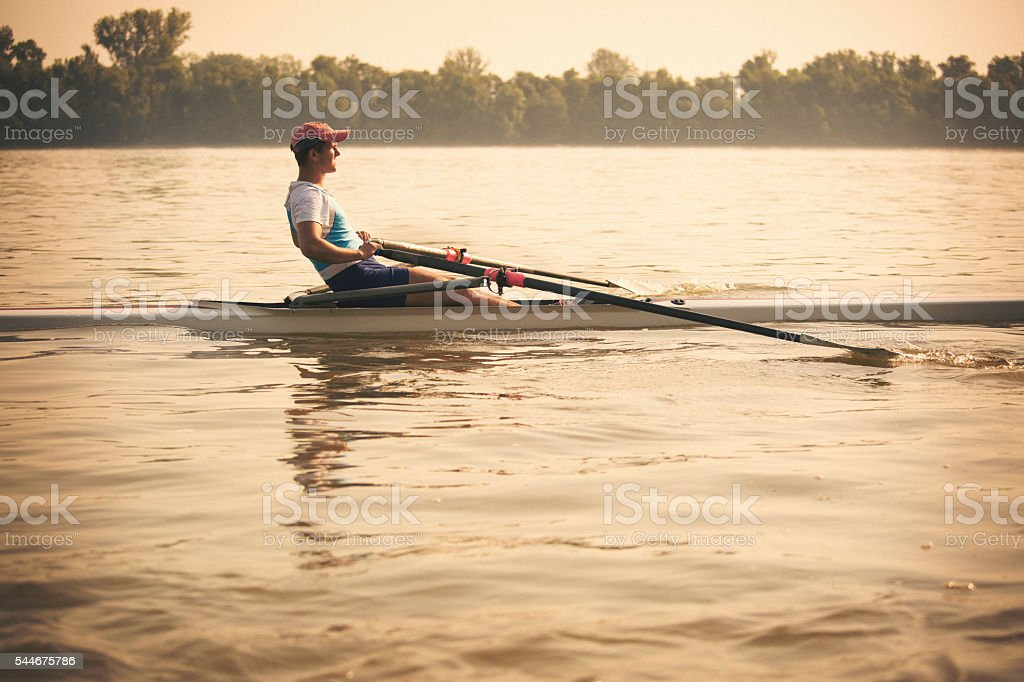 Young man on the river rowing stock photo