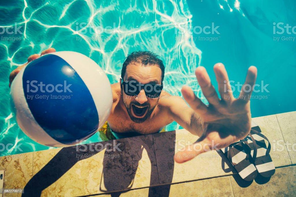 Young man on the swimming pool having fun. stock photo