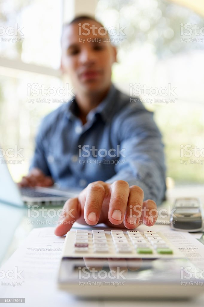 Young Man On Using Calculator At Home royalty-free stock photo