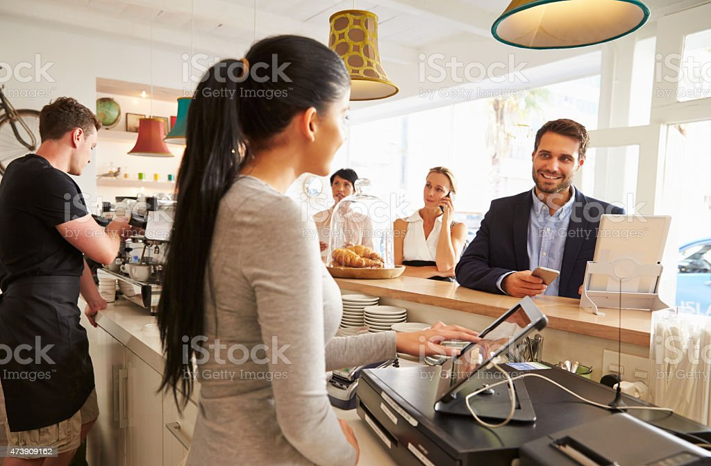 Young man ordering at the counter in a cafe stock photo