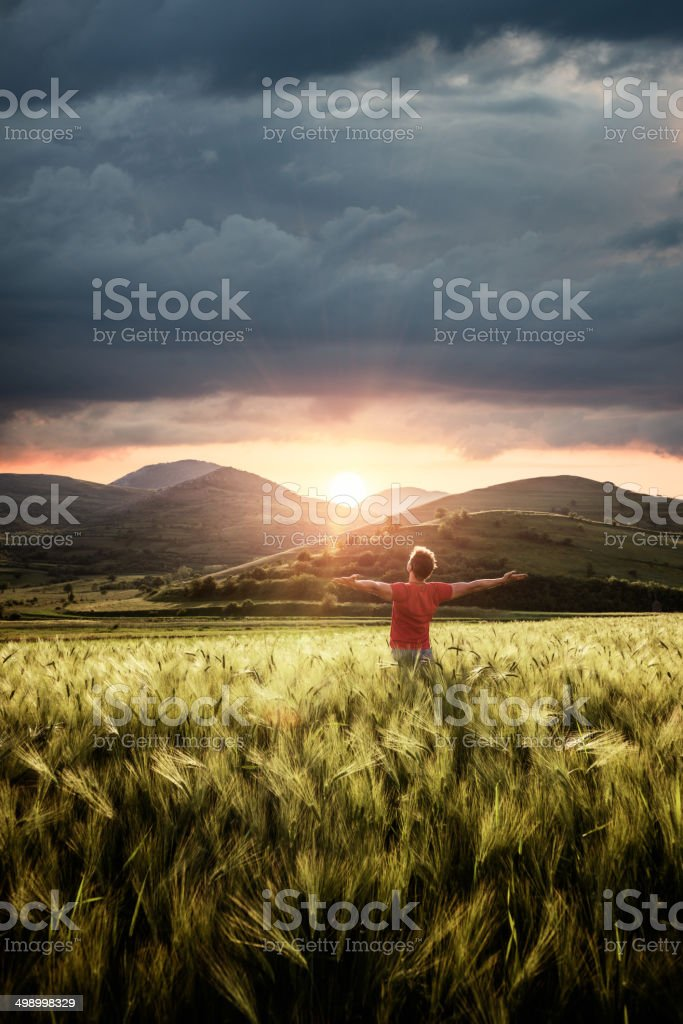 Young man outdoor with hands raised enjoing the sunset stock photo
