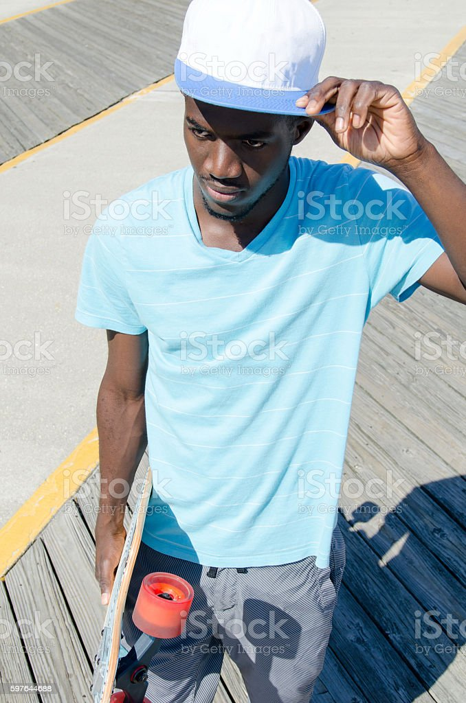 Young man outdoors with his skateboard stock photo
