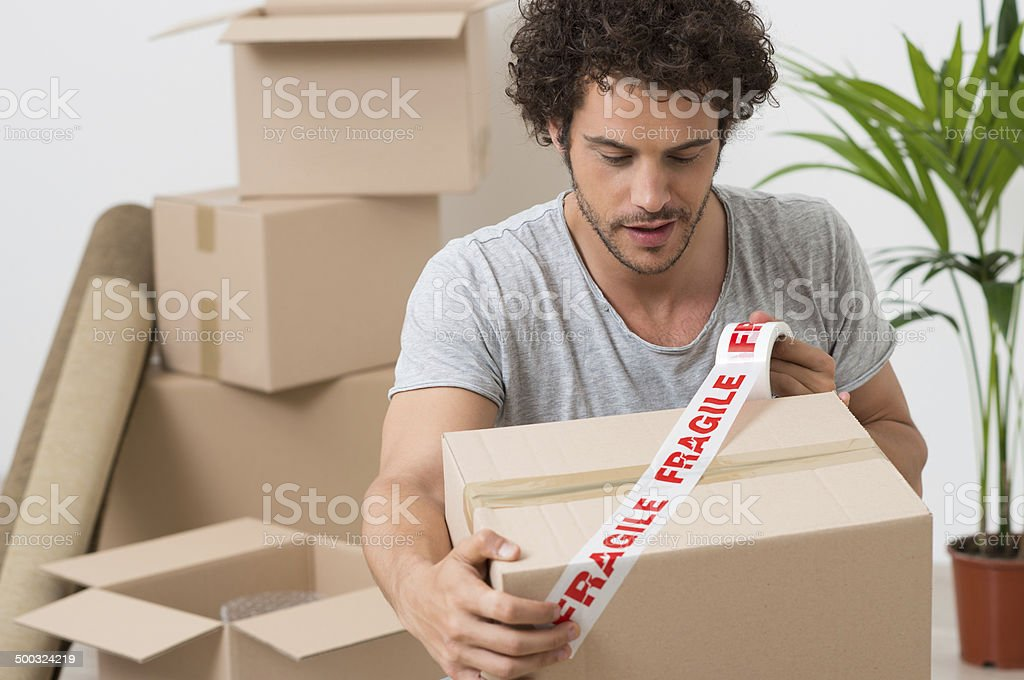 Young Man Packing Cardboard Box stock photo