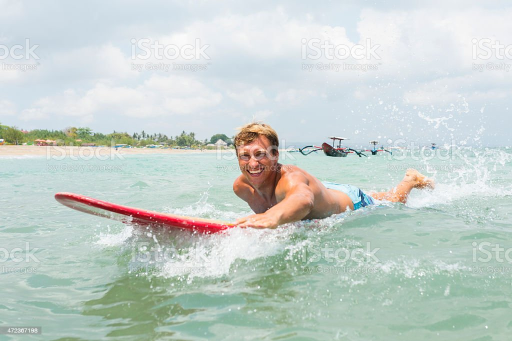 Young Man Paddling a Surfboard Surfing stock photo