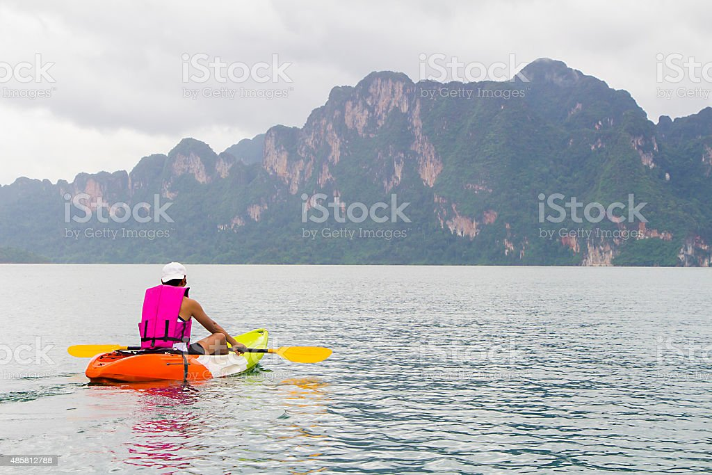 Young man paddling in Chiewlarn dam in Surat Thani, Thailand stock photo