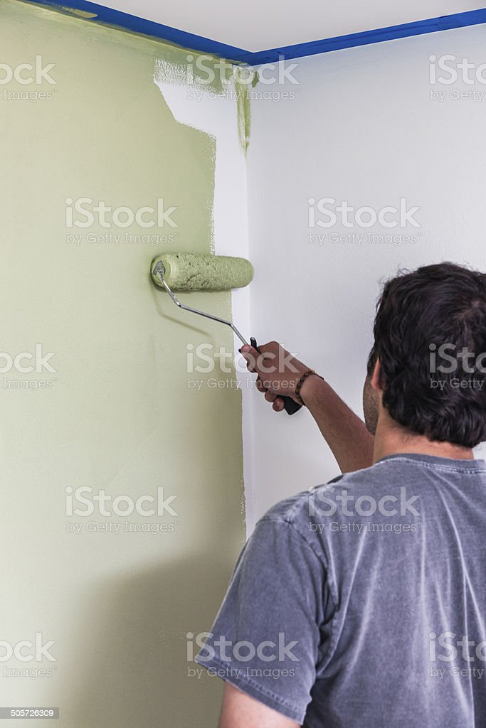 Young Man Painting Bedroom Wall stock photo