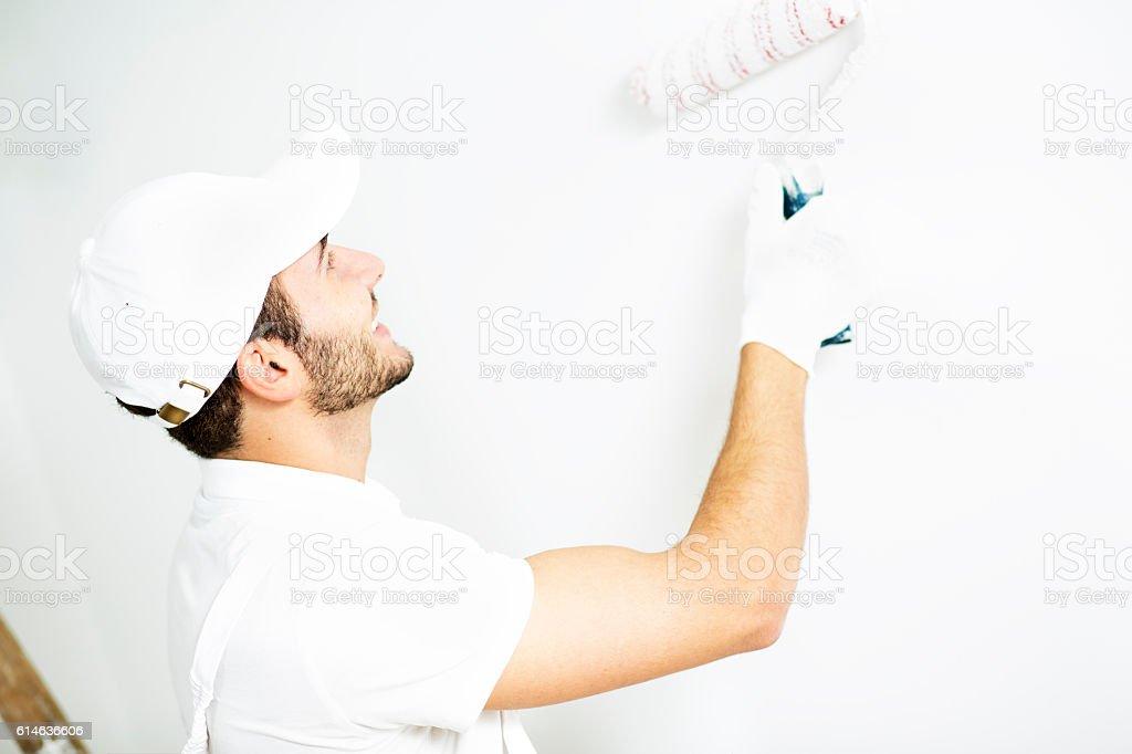 Young man painting walls. stock photo