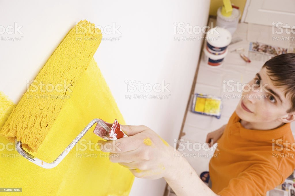 Young man paints the wall in a new house royalty-free stock photo