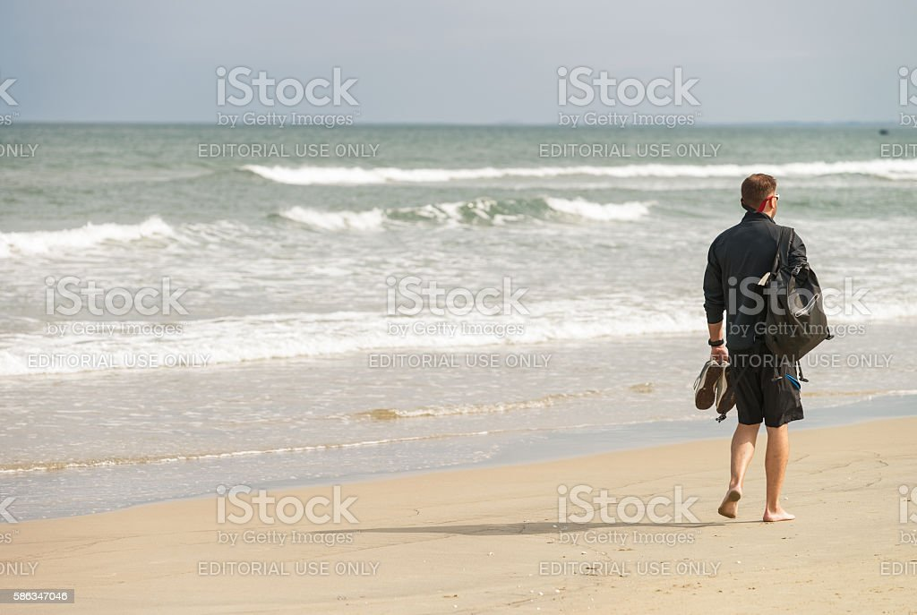 Young man passing by at the China Beach of Danang stock photo