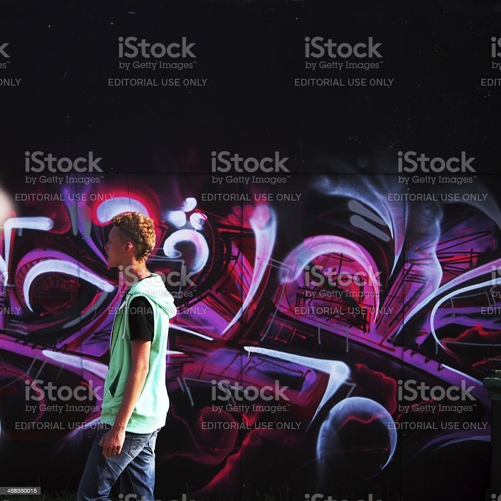 Young man passing graffiti on music-festival in Denmark stock photo