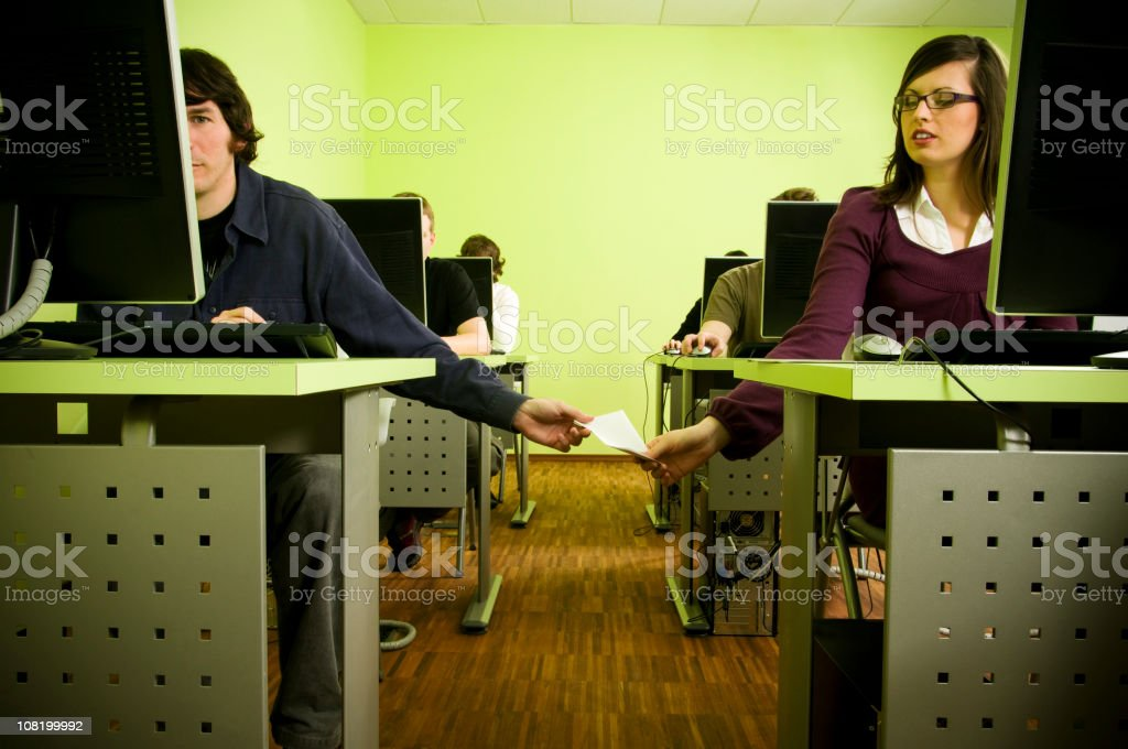 Young Man Passing Woman Note During Class stock photo