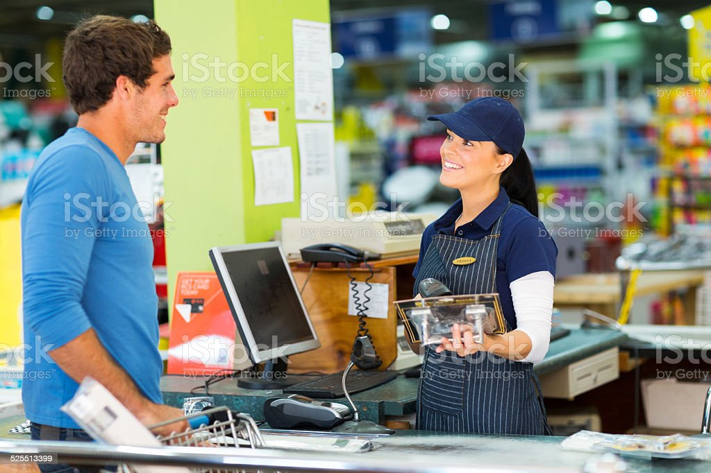 young man paying at till point in hardware store stock photo