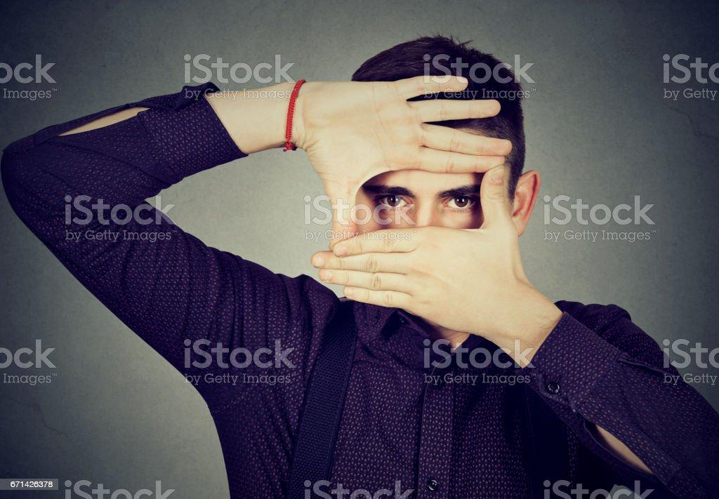 Young man peeking through his fingers hands stock photo