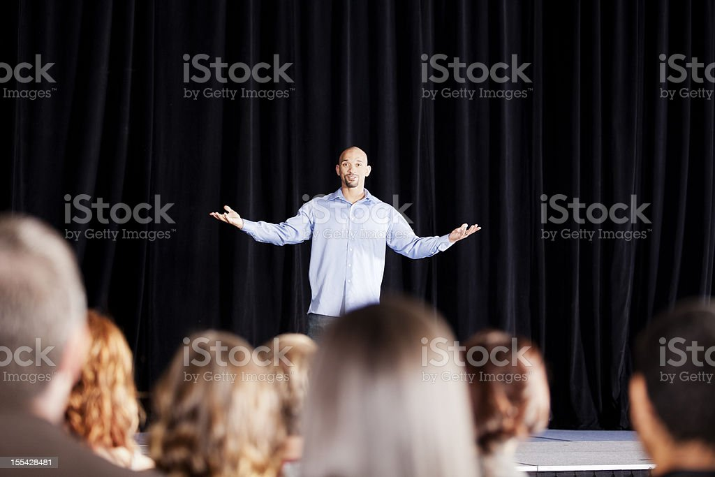 Young man performing on stage for an audience stock photo