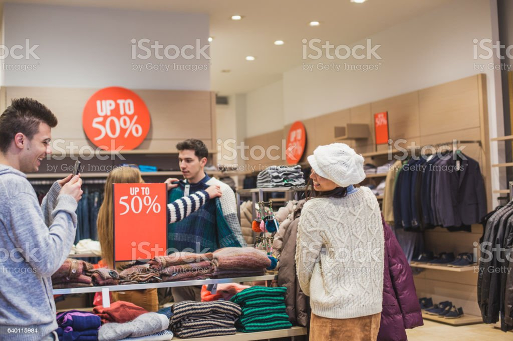 Young man photographing his girlfriend while shopping stock photo