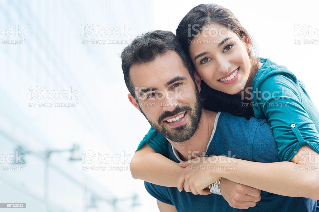 Young man piggyback her girlfriend stock photo