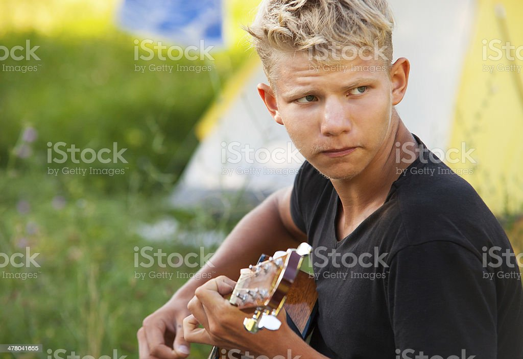Young man plaing by guitar royalty-free stock photo