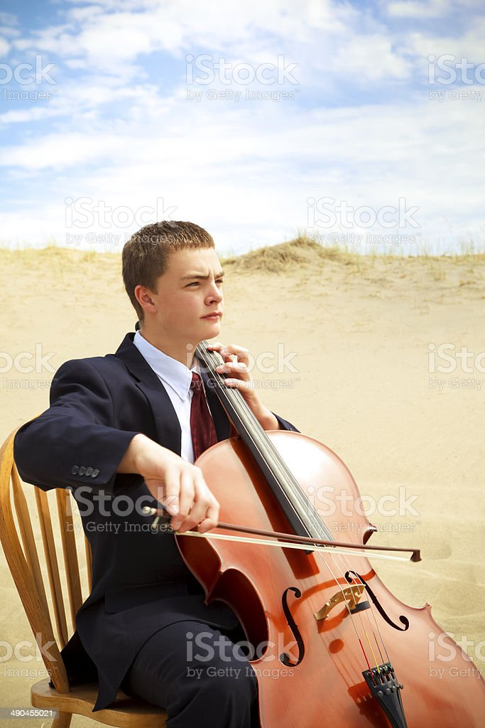 Young man playing a cello in the desert stock photo