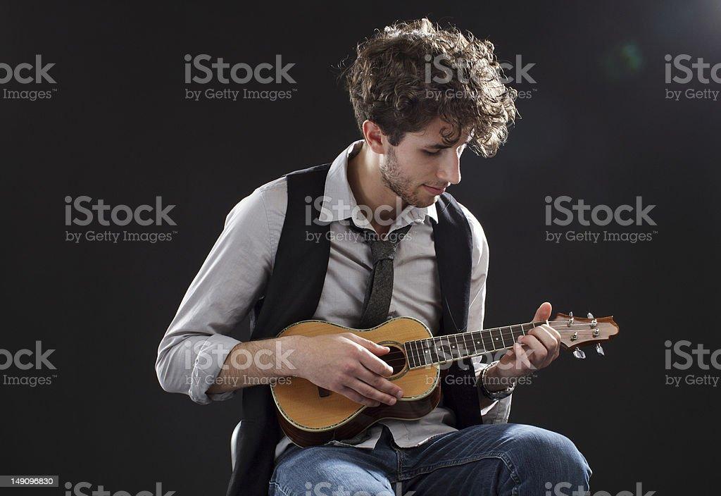 Young man playing a ukulele stock photo