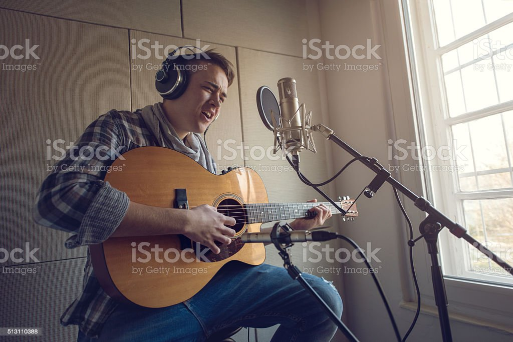Young man playing acoustic guitar and singing in recording studio. stock photo