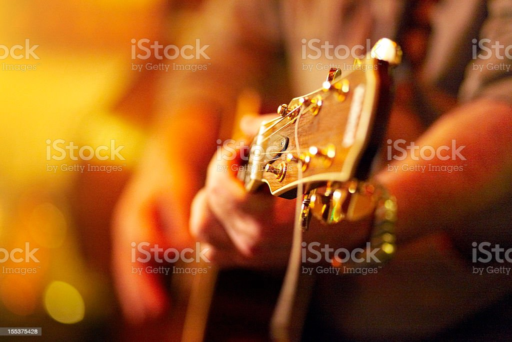 young man playing acoustic guitar in concert stock photo