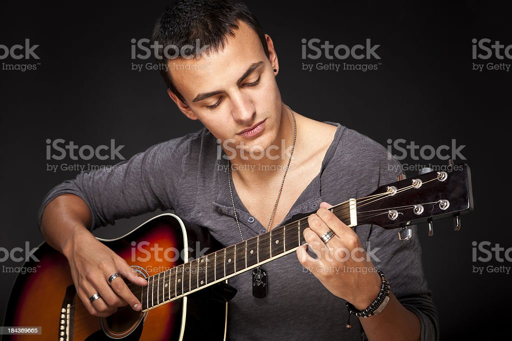 Young man playing acoustic guitar royalty-free stock photo