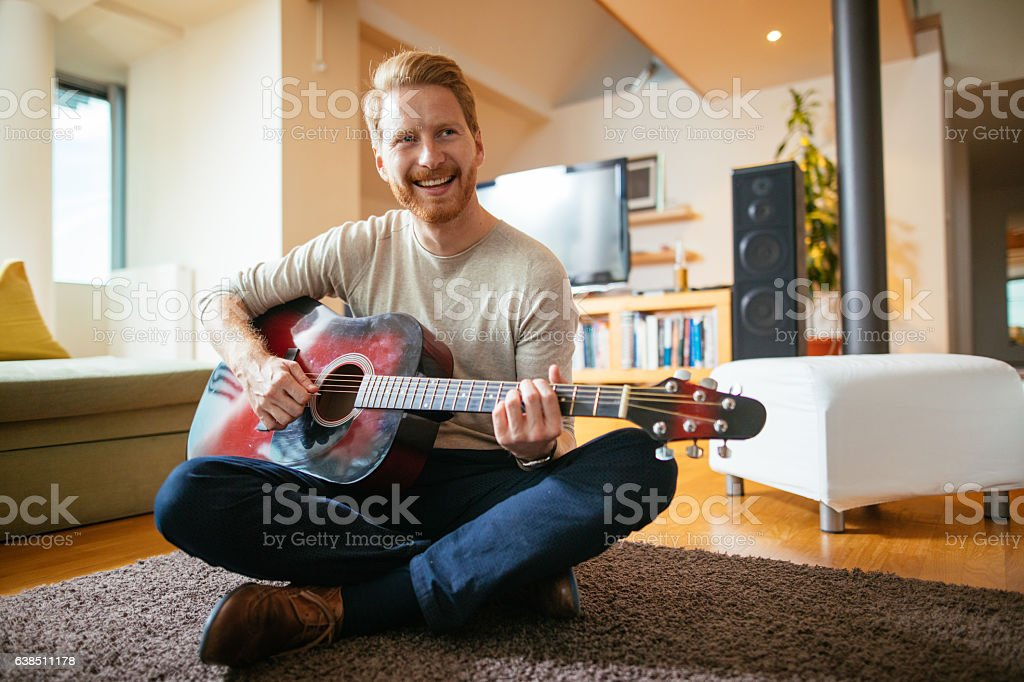 Young man playing acoustic guitar stock photo