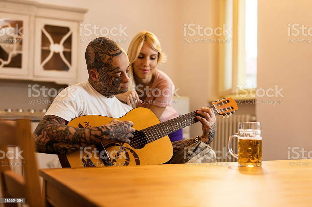 Young man playing acoustic guitar to his girlfriend at home. stock photo