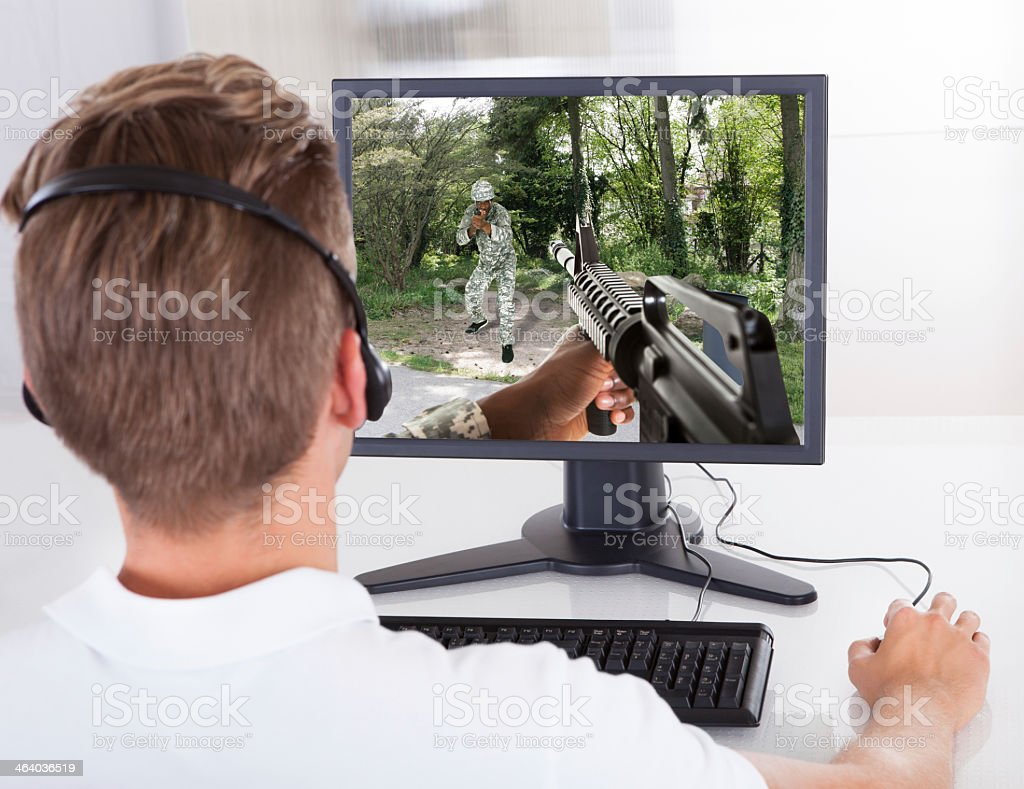 Young man playing an army game on the computer stock photo