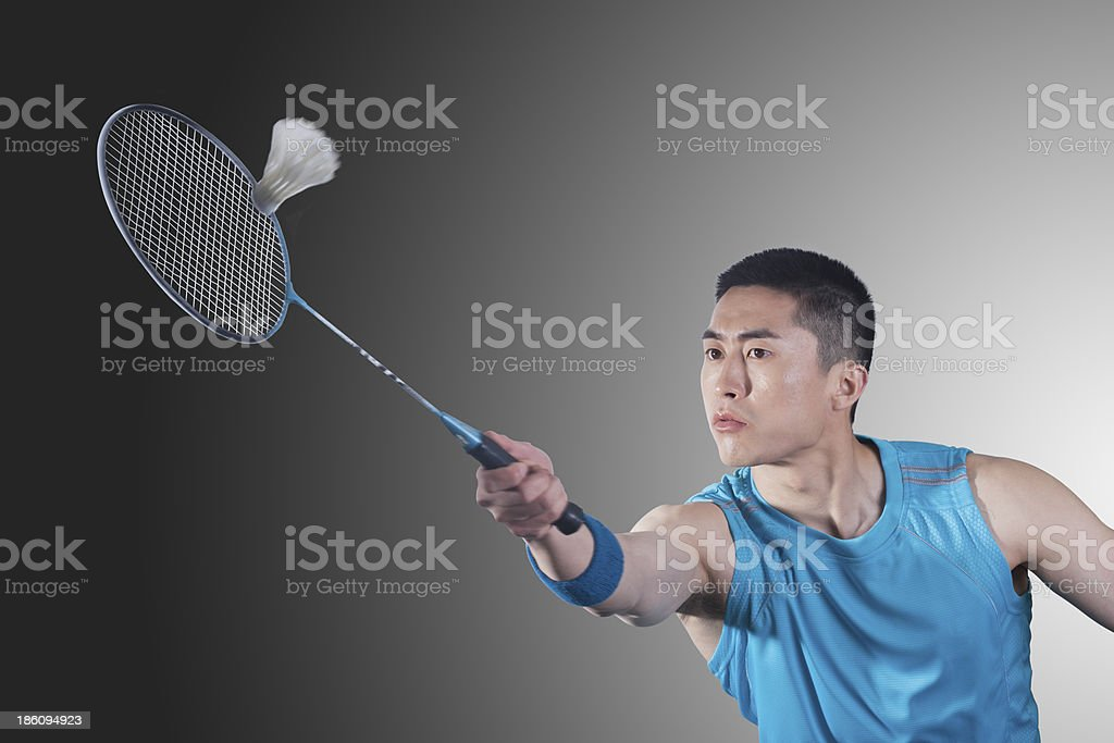 Young man playing badminton, hitting royalty-free stock photo