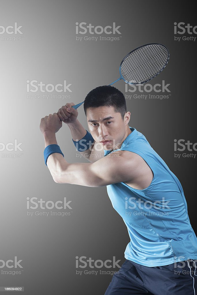 Young man playing badminton, racket raised royalty-free stock photo