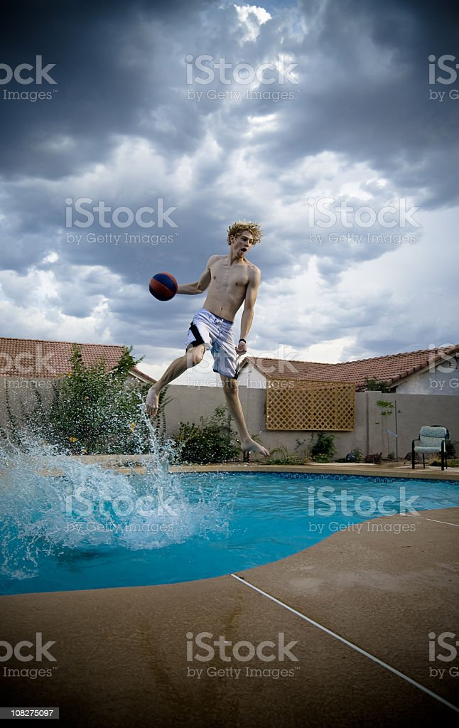 Young Man Playing Basketball in Swimming Pool royalty-free stock photo