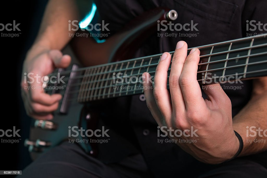 Young man playing electric guitar on dark background stock photo