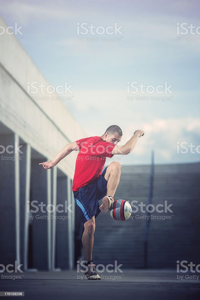 Young man playing football in urban area royalty-free stock photo